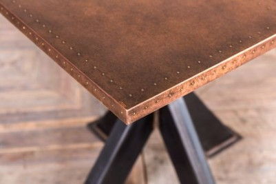 copper top table with tank trap base
