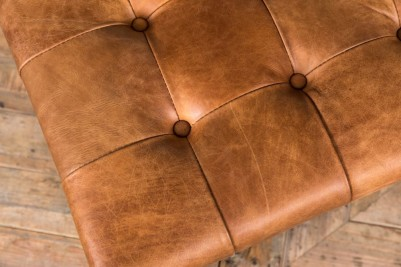 light brown leather footstool with button detail